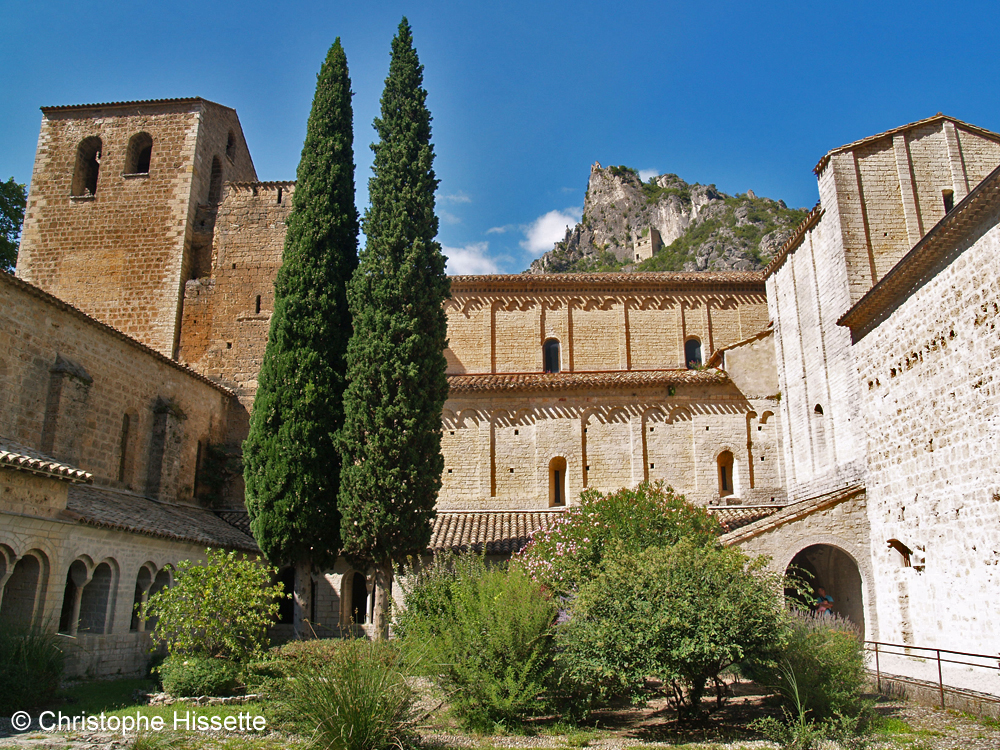 Cloister of the Abbey of Gellone with view on Château du Géant (UNESCO World Heritage - Camino de Santiago), Saint-Guilhem-le-Désert, France