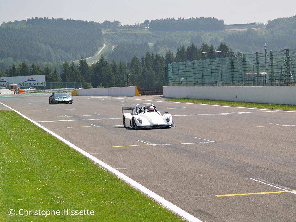 Radical SR3 RSX et Lamborghini dans la ligne droite devant les paddocks